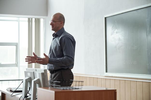 Professeur mature chauve confiant dans des vêtements décontractés intelligents debout près d'un bureau devant le public et expliquant le sujet de la conférence aux étudiants