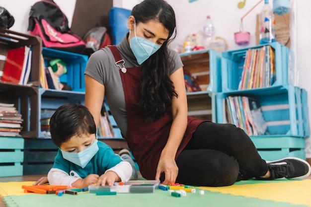 Professeur mexicain avec masque facial prenant soin et jouant avec bébé avec masque facial à l'intérieur de l'école
