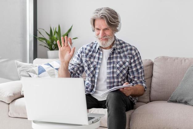 Professeur à mi-tir agitant à l'ordinateur portable