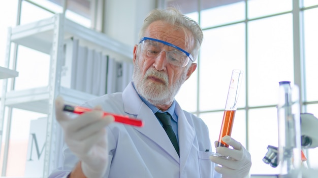Professeur principal chercheur masculin teste un tube liquide chimique avec une concentration faciale