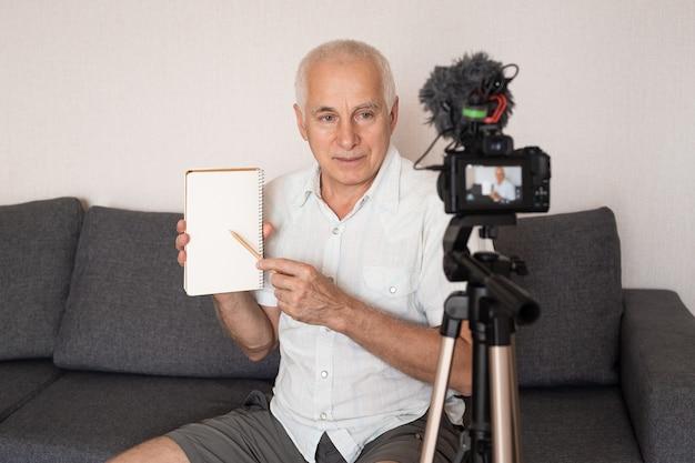 Professeur principal faisant une vidéo pour un blog à la maison à l'aide d'une caméra vidéo, éducation en ligne