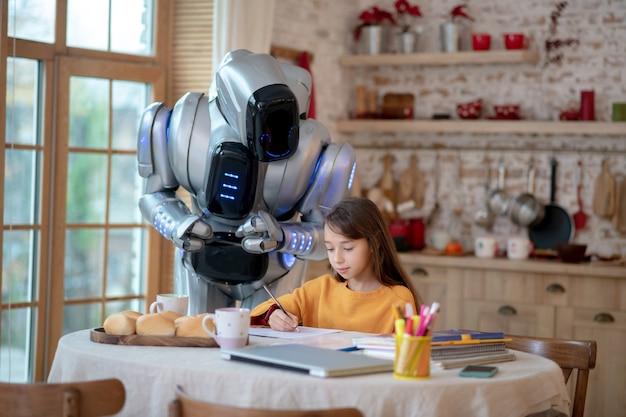 Professeur de robot regardant attentivement comment la fille écrit