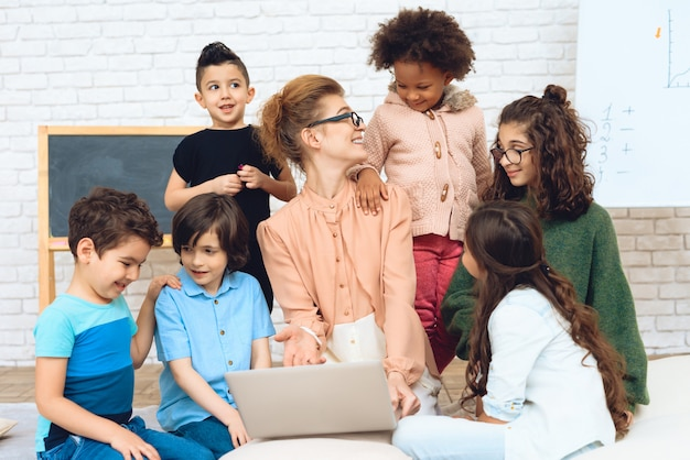 Le professeur s'assoit avec des écoliers qui l'ont entourée.