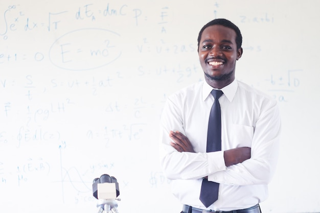 Professeur de sciences africain enseignant et souriant dans la classe de tige au microscope.