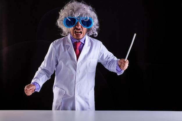 Professeur de sciences en colère en blouse blanche avec des cheveux hirsutes dans des lunettes drôles tenant une baguette pour pointer vers le tableau noir