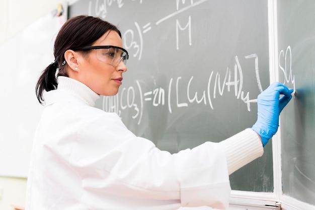 Professeur de sciences écrit sur tableau noir