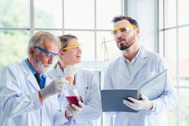 Professeur de sciences et équipe d'étudiants travaillant avec des produits chimiques en laboratoire
