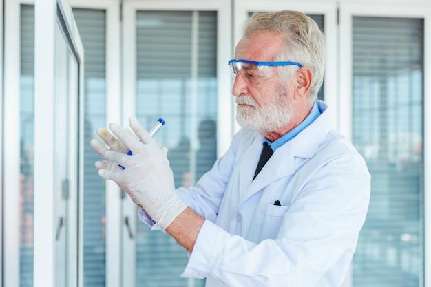 Professeur de sciences hommes travaillant avec des produits chimiques de panneau de verre transparent en laboratoire