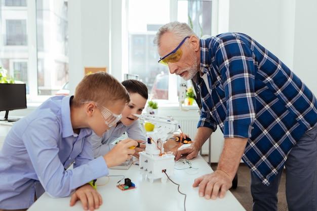 Professeur de sciences. sérieux homme intelligent debout à la table tout en regardant ses élèves travaillant