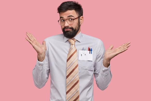 Un professeur de sexe masculin désemparé a un regard hésitant perplexe, étend les paumes d'indignation, porte une chemise formelle, une cravate et des lunettes, a un chaume sombre
