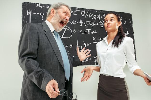 Professeur de sexe masculin et jeune femme contre le tableau noir en classe