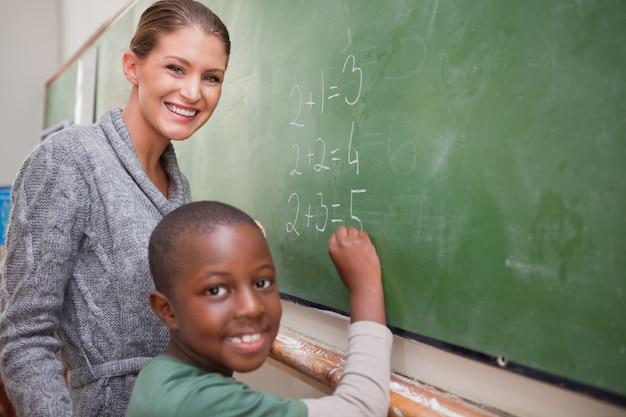 Professeur souriant et un élève faisant un ajout