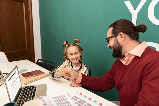 Professeur sympathique. jolie fille blonde portant des bracelets sur sa main, passant son temps à l'école avec son professeur