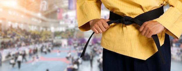 Professeur de taekwondo ceinture noire grand maître tenir et attacher la pose de ceinture, studio de partie de taille sur la zone du stade de compétition internationale en arrière-plan