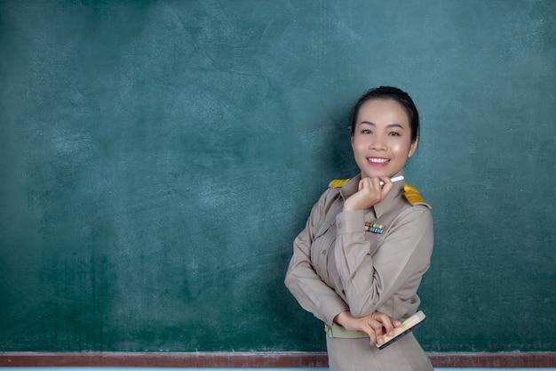 Professeur thaïlandais heureux en tenue officielle posant devant le tableau noir