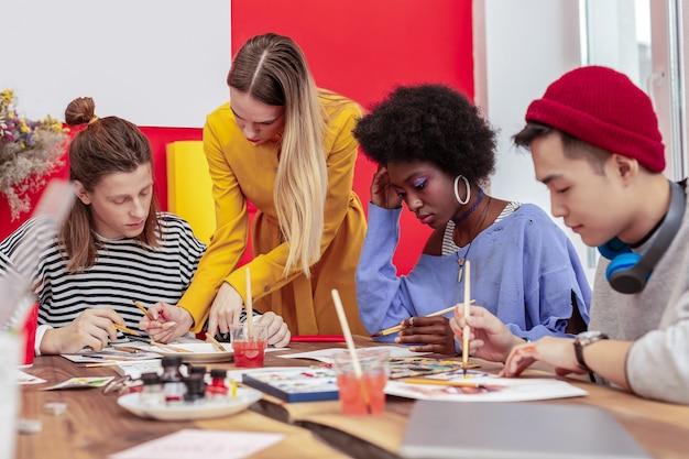 Professeur utile. professeur aux cheveux blonds utile aidant ses étudiants en art dans le processus de travail