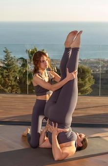 Professeur de yoga complet aidant l'élève