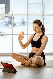 Professeur de yoga menant un cours de yoga virtuel à la maison lors d'une conférence vidéo
