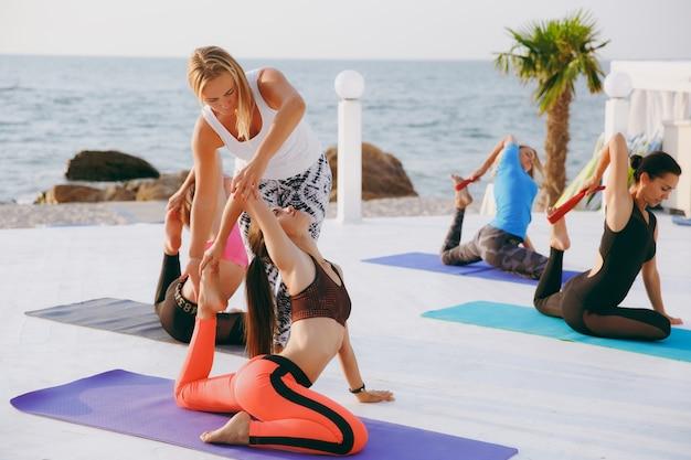 Le professeur de yoga montre aux filles comment faire correctement la pose