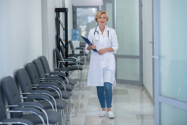 Profession médicale. sourire blonde femme médecin avec stéthoscope marchant le long du couloir