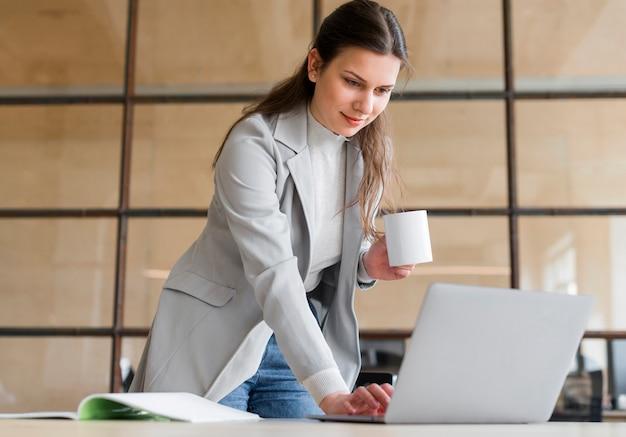 Professional jeune femme souriante tenant une tasse de café blanc travaillant sur ordinateur portable