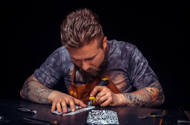 Professional tanner effectue le travail du cuir pour un nouveau produit.