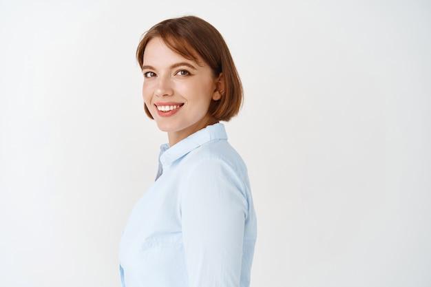 Professionnel des affaires. portrait d'une jeune femme confiante en blouse de bureau, tourne la tête et souriante, sûre d'elle, debout sur un mur blanc