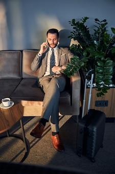 Professionnel d'affaires vérifiant l'heure tout en parlant au téléphone
