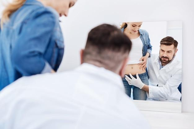 Professionnel beau beau médecin regardant dans le miroir et pointant vers l'estomac de ses clients tout en définissant ses zones à problèmes