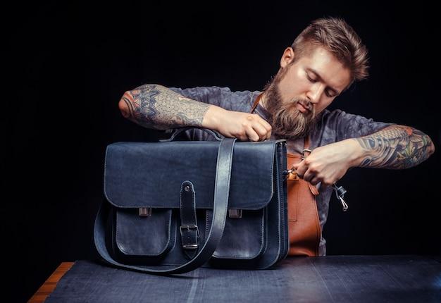 Le professionnel du cuir effectue le travail du cuir pour un nouveau produit