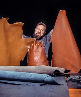 Professionnel du cuir fabriquant de nouveaux produits en cuir sur son lieu de travail.