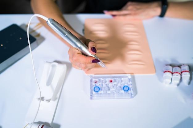 Professionnel. formation de spécialiste ou de stagiaire assurant le tatouage permanent sur les fausses lèvres. matériel de formation en caoutchouc.