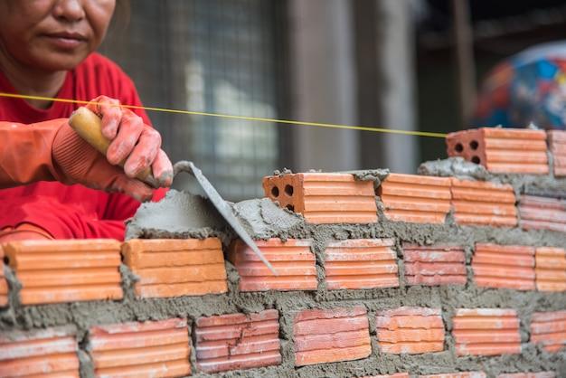 Professionnel installant la brique rouge dans le chantier de construction.