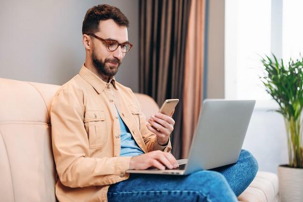 Professionnel jeune homme intelligent dans des verres détient un ordinateur portable et un smartphone