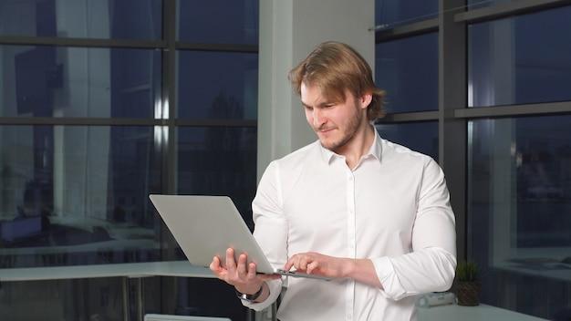 Professionnel masculin faisant des achats travaillant sur ordinateur portable au bureau.