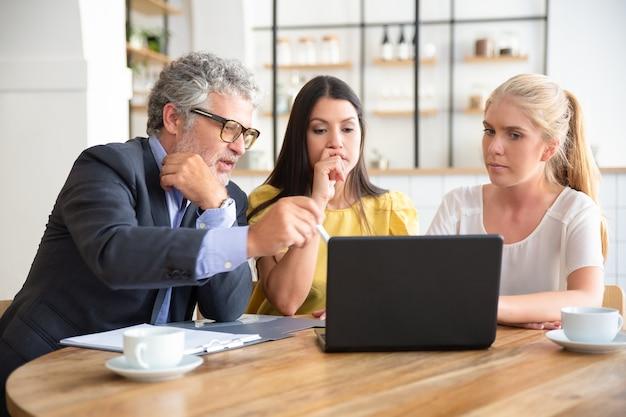 Professionnel mature expliquant les détails du projet aux jeunes clients, pointant sur l'affichage du pc