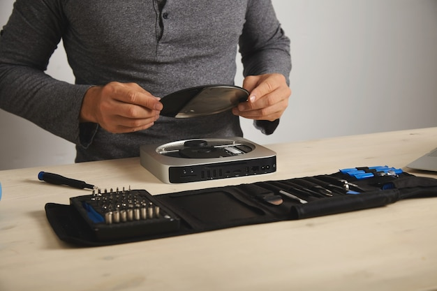 Le professionnel ouvre le topcase du petit ordinateur personnel avant d'augmenter la mémoire, vue grand angle