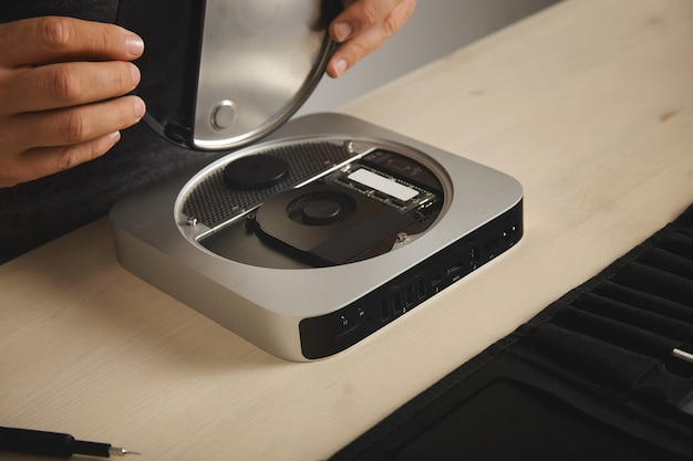Le professionnel ouvre le topcase du petit ordinateur personnel avant d'augmenter la mémoire