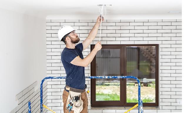 Professionnel en salopette avec des outils sur le fond du site de réparation pleine longueur. concept de rénovation domiciliaire.