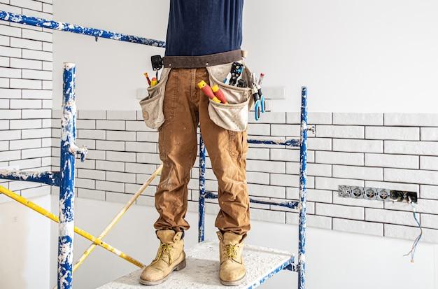 Professionnel en salopette avec des outils sur le fond du site de réparation.