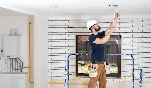 Professionnel en salopette avec des outils sur le site de réparation. concept de rénovation domiciliaire.