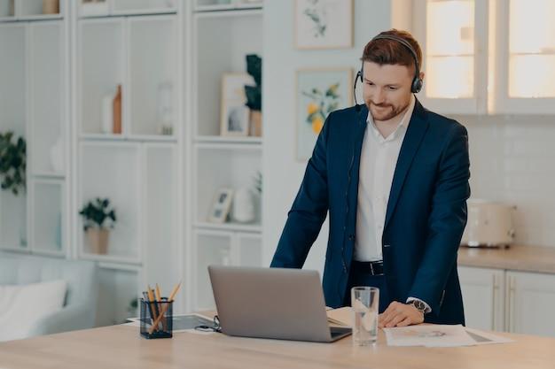 Professionnel souriant portant un costume et un casque, écoutant attentivement son collègue lors d'un appel vidéo sur un ordinateur portable, debout près de la table dans la cuisine tout en participant à une réunion en ligne