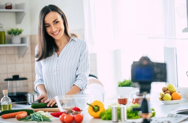 Professionnelle belle jeune femme heureuse blogue pour sa chaîne de cuisine sur la vie saine dans la cuisine de sa maison et à la recherche de l'appareil photo sur un trépied