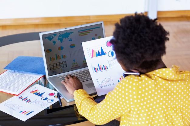 Professionnels des affaires. femme d'affaires analysant les données à l'aide d'un ordinateur tout en passant du temps au bureau