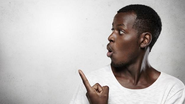 Profil de beau client ou employé africain étonné montrant un contenu étonnant ou choquant, pointant son doigt sur un mur de béton vierge avec un espace de copie pour votre publicité
