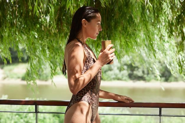 Profil d'un beau modèle athlétique debout près du rivage, regardant droit devant, portant un maillot de bain léopard, ayant de longs cheveux noirs, concentré, tenant un cocktail dans une main.