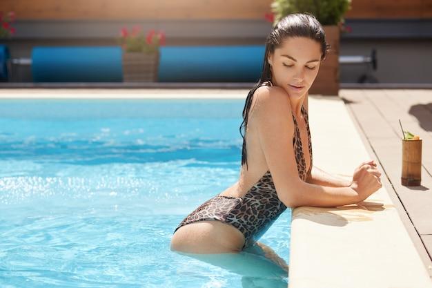Profil de beau modèle sexy posant dans la piscine pendant les vacances d'été