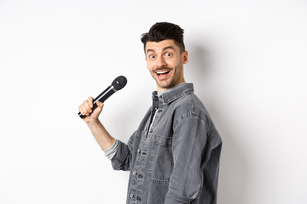 Profil de bel homme souriant tenant micro, tourner la tête à la caméra avec le visage excité, chanter le karaoké et effectuer le stand-up, debout sur fond blanc.