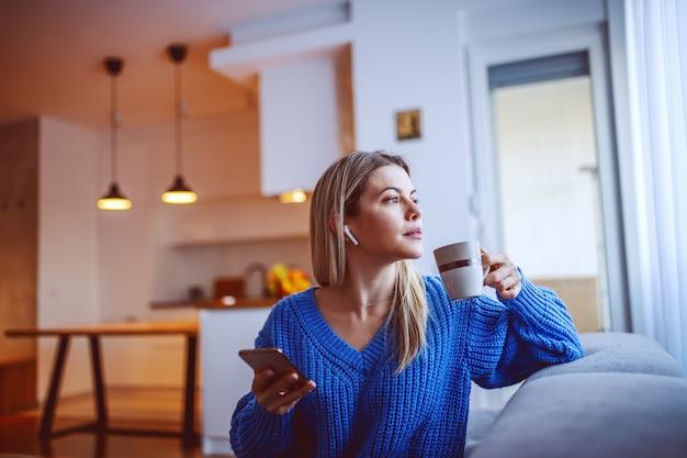 Profil de la belle blonde caucasienne pensive, buvant du café et utilisant un téléphone intelligent tout en étant assis dans le salon sur le canapé et en regardant la fenêtre de l'auge. dans les oreilles se trouvent des écouteurs à dents bleues.