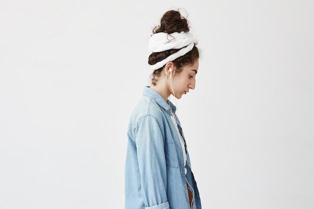 Profil de belle femme aux cheveux ondulés en chignon, vêtue d'une chemise en jean sur une chemise blanche, avec des écouteurs blancs, écoutant ses chansons préférées, appréciant la musique, posant contre le mur blanc